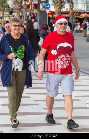 Benidorm, Costa Blanca, Spain, 25th December 2018. British tourists dress for the occasion on Christmas Day in this favourite getaway destination for Brits escaping the cold weather at home. Temperatures will be in the mid to high 20's Celsius today in this mediterranean hotspot. Couple wearing Christmas clothing and santa hats. - Stock Image