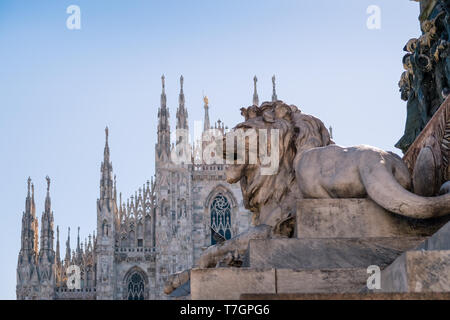 Piazza del Duomo, Milan, Italy. Lion sculpture on Vittorio Emanuele monument, with gothic cathedral spires in the background. - Stock Image