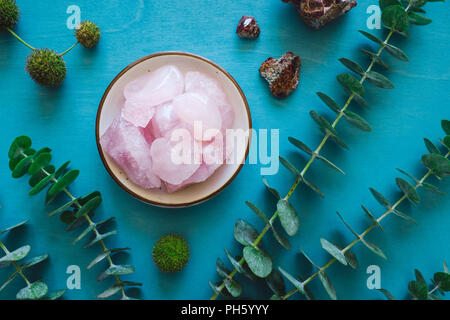 Rose Quartz with Garnet and Eucalyptus on Turquoise Table - Stock Image