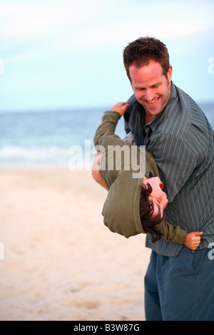 Father and son having a playful moment on a beach - Stock Image