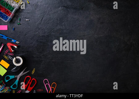 Mix of office supplies on black background. Top view, copy space - Stock Image