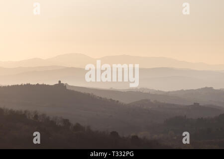 Beautiful view of Tuscany hills at sunset, with mist and warm colors - Stock Image