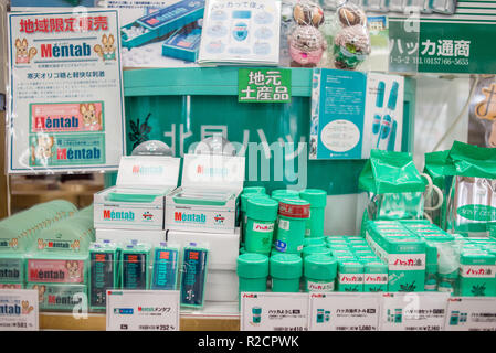 Kitami Peppermint (Hakka) products for trade on display in the window of a convenience store in Kitami, Hokkaido, Japan. The Mint Memorial Museum introduces the history of the Kitami's mint industry, with which the city has prospered. In the first half of the 20th century, 70% of the world's mint was produced in Kitami. - Stock Image