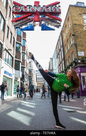 """London, UK. 18th March, 2019. Taekwondo World Champion Samira El Idrissi marks the celebration of the second annual Global Recycling Day beneath the Carnaby Street sign. This year's theme is """"Recycling into the Future"""", focusing on the importance and power of youth, innovation and education in ensuring a brighter future for the planet. Global Recycling Day is intended as a day for driving global change, changing people's perceptions about recycling, highlighting it as a global responsibility and encouraging recyclable materials to be viewed as a vital 'Seventh Resource'. Credit: Mark Kerrison/ - Stock Image"""