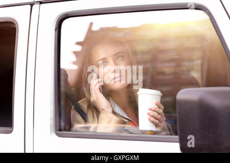 Portrait of a beautiful serious business woman having coffee in the car, going to work and talking on the phone - Stock Image