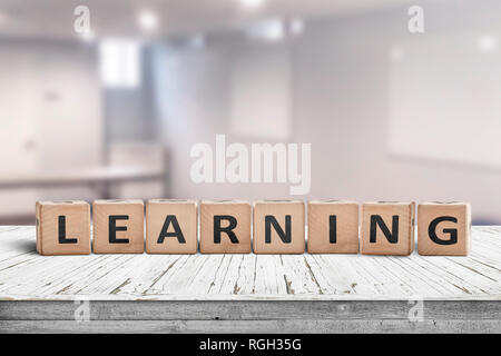 Learning in a classroom with a sign on a wooden table in a bright room - Stock Image