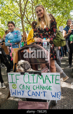 London, UK. 12th May 2019. A woman with a dog in a pushchiar with a poster waits for the start of the march by several thousand mothers, children and some fathers behind 11-year-olds and 3 giant push chairs with stilt walkers from Hyde Park Corner to a rally filling Parliament Square, backing Extinction Rebellion's call for the drastic and urgent action needed to avert the worst consequences of climate change, including possible human extinction. Our politicians have declared a climate emergency but now need to take real action rather than continuing business as usual which is destroying life  - Stock Image