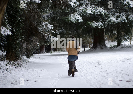 A woman walking down a path in a snow covered forest - Stock Image