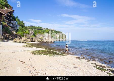 Fisherman carrying a net walking along Bingin beach, Bali, Indonesia - Stock Image
