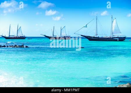 Arashi Beach, Aruba, Caribbean Sea in January 2018: 3 tour boats anchored for tourists to go swimming or snorkeling. - Stock Image