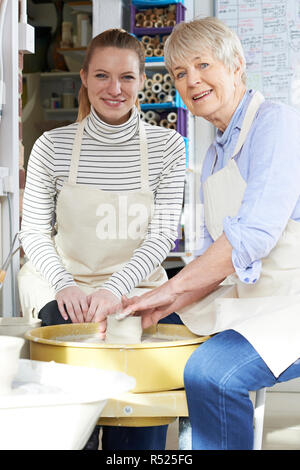 Portrait Of Senior Woman With Teacher In Pottery Class - Stock Image