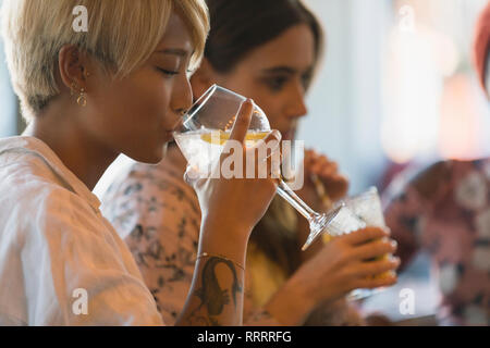 Young woman drinking cocktail in bar - Stock Image