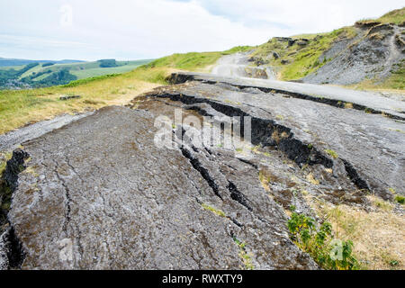 Road damage due to landslide. Part of the now abandoned A625 road below Mam Tor, Derbyshire, England, UK - Stock Image