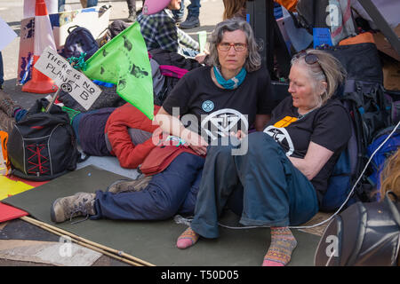London, UK. 19th April 2019. People sit around to protect the large pink yacht, named after Honduran environmental activist Berta Cáceres, assassinated in 2016 before Emma Thompson arrives to speak as a part of the activities to show 'Love For The Earth' on the 5th day of the occupation, but which were interrupted by police shortly after she spoke. Credit: Peter Marshall/Alamy Live News - Stock Image