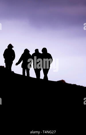 Walkers seen in silhouette as they walk in evening light. - Stock Image