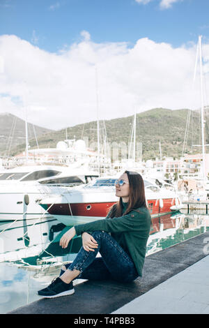 A beautiful young girl in sunglasses is sitting next to the yachts in Porto Montenegro in Tivat in Montenegro resting and looking at the yachts. - Stock Image