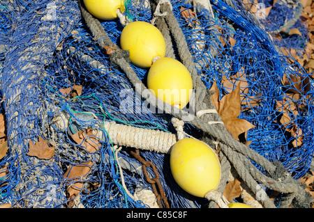 Fischernetz mit gelben Schwimmern zum Trocknen ausgelegt.   Fishing net with yellow floats laid out to dry. - Stock Image