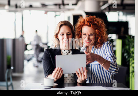 Two serious female business people with tablet sitting in an office, talking. - Stock Image