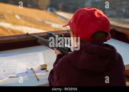 A 12-year old boy holds a 22 caliber rifle during a safety lesson in the United States. - Stock Image