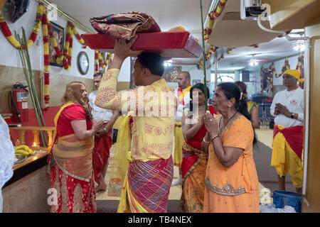 A Hindu woman in her late 70's & her family bring offerings to the deities as a gesture of thanks for the good things in her life. - Stock Image