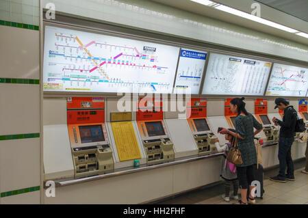 Passengers buying tickets for the Minatomirai Line subway at ticket vending machines. Yokohama, Japan. - Stock Image