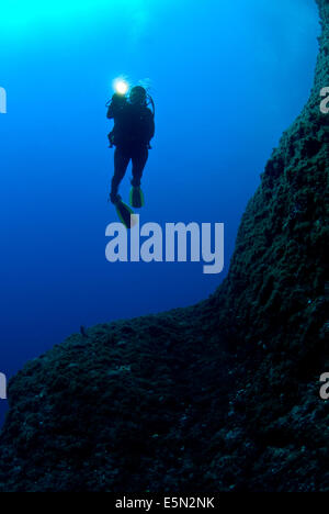 young female diver swimming iin blue water along reef wall using dive torch. - Stock Image