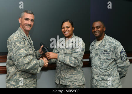 "U.S. Air Force Col. Daniel Lasica, 20th Fighter Wing (FW) commander, left, and Chief Master Sgt. Christopher McKinney, 20th FW command chief, right, recognize Senior Airman Tamika Bradley, 20th Medical Operations Squadron allergy and immunization technician, center, as the Shaw ""Weasel of the Week"" at Shaw Air Force Base, S.C., March 29, 2017. Bradley helped Shaw reach 100 percent flu vaccine compliance, placing Shaw as number one in the Air Force. (U.S. Air Force photo by Airman 1st Class Destinee Sweeney) - Stock Image"