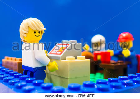 Poznan, Poland - February 27, 2019: Lego cashier standing behind a cash machine on a desk in a restaurant with eating people in soft focus background. - Stock Image
