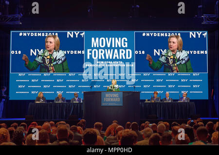 Long Island, USA. 23rd May, 2018. HILLARY CLINTON  delivers Keynote Address during Day 1 of New York State Democratic Convention, held at Hofstra University on Long Island. Clinton, the former First Lady and NYS Senator, endorsed the re-election of Gov. A. Cuomo for a third term, and mentioned how Hofstra was the site of her first 2016 debate with Trump. NYS Democratic Leaders on stage include CHRISTINE QUINN, Exec. Committee Chair, sitting to right of Clinton. Credit: Ann E Parry/Alamy Live News - Stock Image
