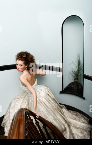A beautiful bride descends down a staircase wearing a couture dress. - Stock Image