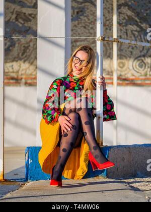 Young woman legs heels enjoying sun smiling at camera squinting eyes - Stock Image