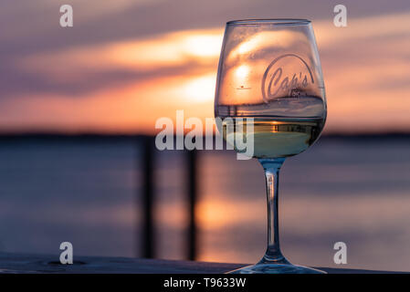 Colorful sunset view with wine glass on the waterfront dock at Caps on the Water, a local seafood restaurant in St. Augustine, Florida. (USA) - Stock Image
