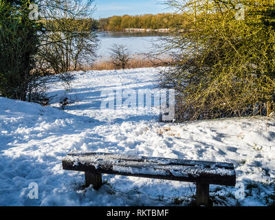 A snow-covered bench overlooking the lake at Coate Water in Wiltshire. - Stock Image