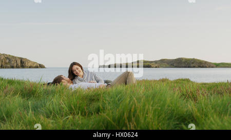 Smiling boyfriend and girlfriend laying in grassy field near lake in remote landscape under blue sky - Stock Image
