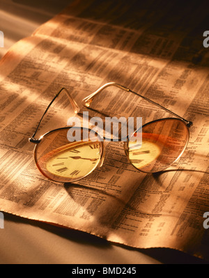 Glasses on the Financial Times with Reflected Clock - Stock Image