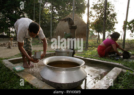 BANGLADESH Early morning ablutions for a Garo tribal minority family of Haluaghat, Mymensingh region photo by Sean Sprague - Stock Image