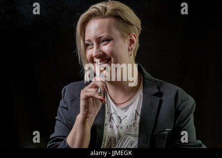 Happy and smiling woman holding electronic cigarette between her teeth - Stock Image