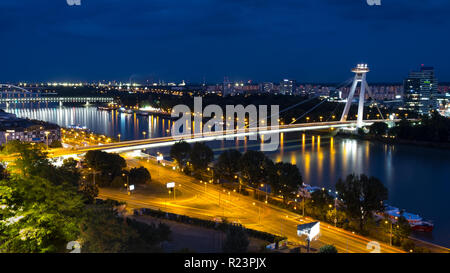 Night time view of Danube river in Bratislava, Slovakia, featuring Most SNP bridge.  Trail of car lights visible on streets - Stock Image