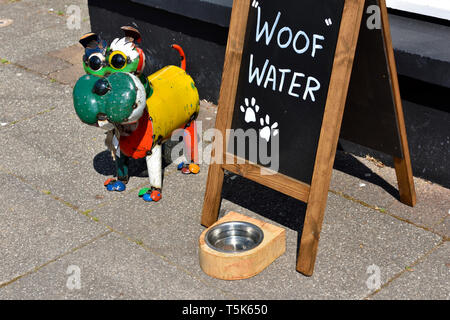 """Dog watering dish with sign """"Woof Water"""" outside shop on pavement - Stock Image"""