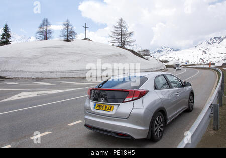Silver Honda Civic car parked at side of E62 Simplonstrasse road on northern side of Simplon Pass in Switzerland with snow banks at side of road - Stock Image