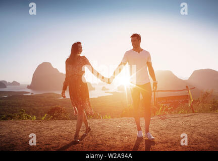 Attractive, relaxed couple posing against an island landscape - Stock Image