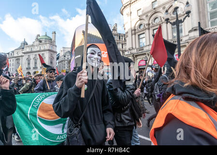 London, UK. 9th Dec, 2018. A protester in an 'Anonymous' mask carries a black flag on the united counter demonstration by anti-fascists in opposition to Tommy Robinson's fascist pro-Brexit march. The march which included both remain and leave supporting anti-fascists gathered at the BBC to to to a rally at Downing St. Police had issued conditions on both events designed to keep the two groups well apart. Credit: Peter Marshall/Alamy Live News - Stock Image