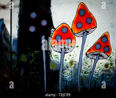 Glass art toadstools at craft market - Stock Image