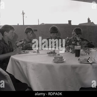 1967, young boys having a meal on the top floor of a multi-car, England, UK. - Stock Image