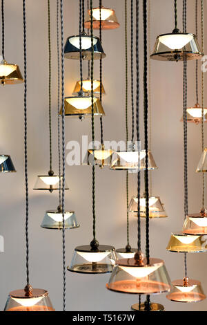 Many modern design chandeliers with glowing lamps, hanging on long black wires against grey wall - Stock Image