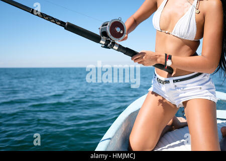 Close up of fishing reel and rod used by attractive young woman on fishing boat - Stock Image