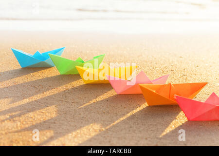 Colored paper boats row on sandy beach outdoors at sunset. Selective focus on front - Stock Image