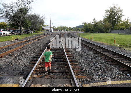 Boy walking along train tracks, Hudson, NY, USA - Stock Image
