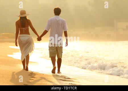 Back view of a couple holding hands walking on the beach at sunrise - Stock Image