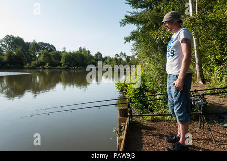 Henlow, Bedfordshire, UK, 25th July 2018. Angler James  set up very early before the heat becomes too much for him. Credit: Mick Flynn/Alamy Live News - Stock Image